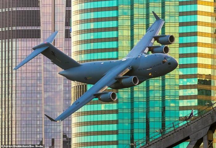 Австралийский истребитель и грузовой самолет летят между небоскребами, показывая невероятное мастерство на фестивале в Брисбене