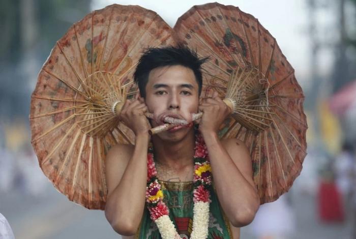 Фанатики просовывают ножи, пистолеты и всё что угодно сквозь свои щеки, когда проходит тайский религиозный праздник