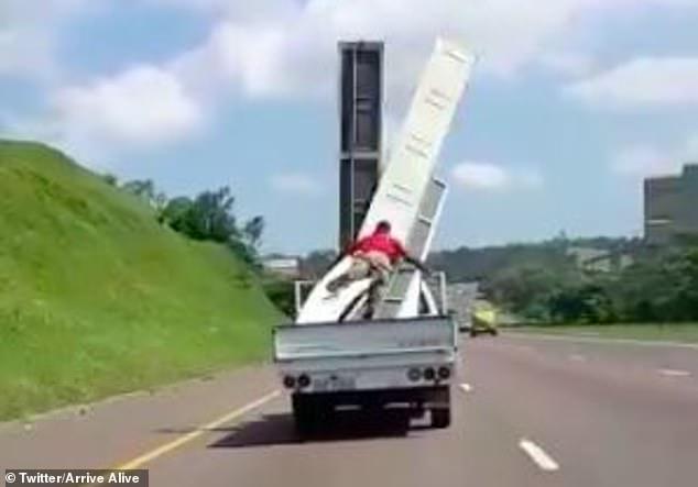 Шокирующий момент рабочего, удерживающего листы в кузове грузовика, сдувает встречным потоком
