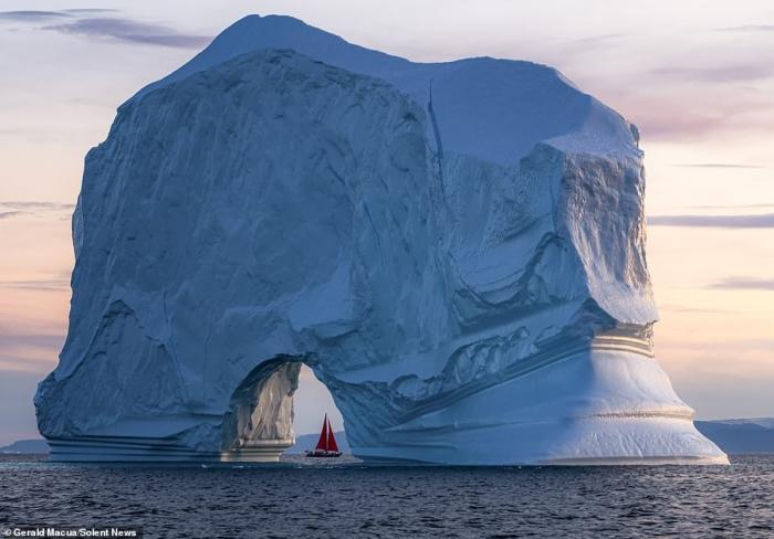 Парусная лодка выглядит крошечной. Она карлик по сравнению с гигантским айсбергом