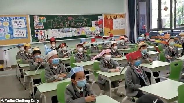 Школьники в Китае должны носить шляпы шириной в один метр, чтобы сохранять безопасную дистанцию в классах