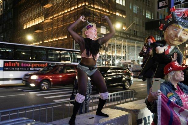 Сексуальная танцовщица, изображающая Трампа и протестующие, сталкиваются с вооруженной полицией у Башни Трампа