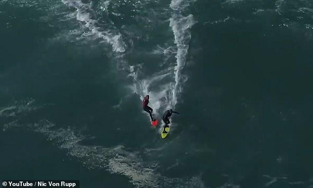 Страшный момент два серфера сталкиваются, когда они едут на одной и той же чудовищной волне в Португалии