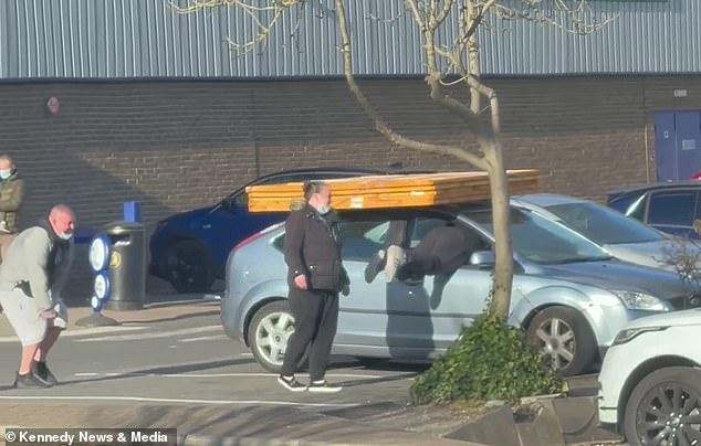 Покупатель магазина «Сделай сам» пытается пролезть через окно автомобиля, потому что двери заклинило. Тяжёлые деревянные панели на крыше