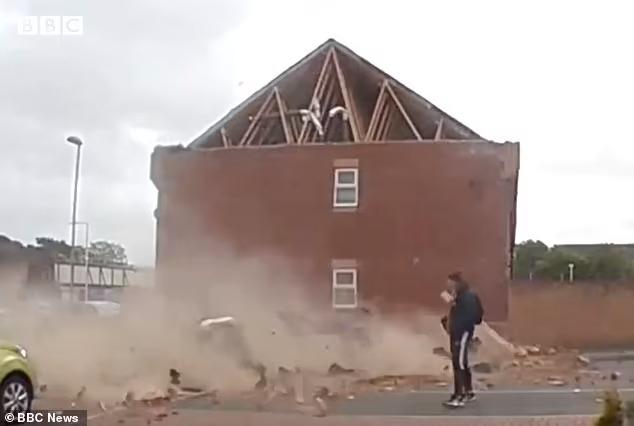 Момент, когда крыша обрушается на припаркованную машину при сильном ветре в Дорсете..., но прохожий едва ускоряет шаг