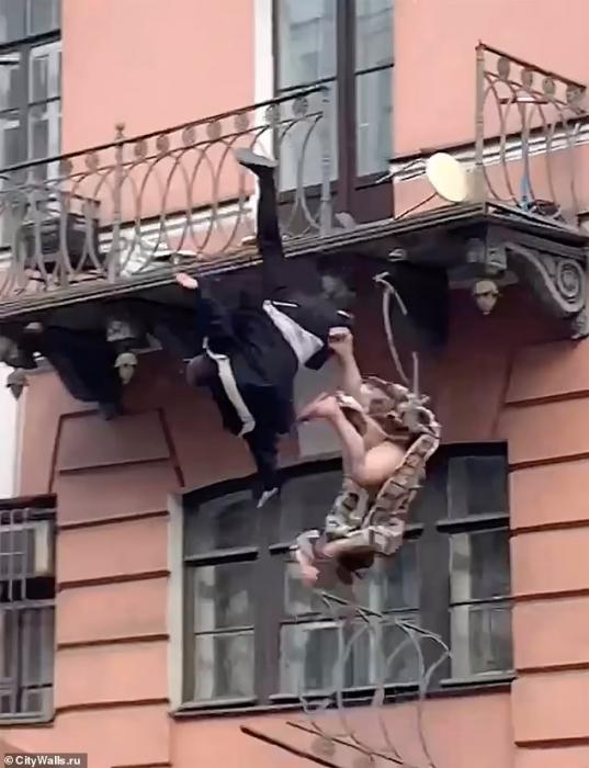 Страшный момент, когда пара падает с балкона после того, как богатые перила на балконе в  Санкт-Петербурге ломаются