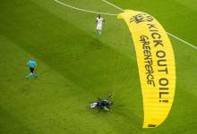 Много футбольных фанатов было госпитализировано, когда парашютист из Гринпис протестуя, приземлился на стадион во время матча